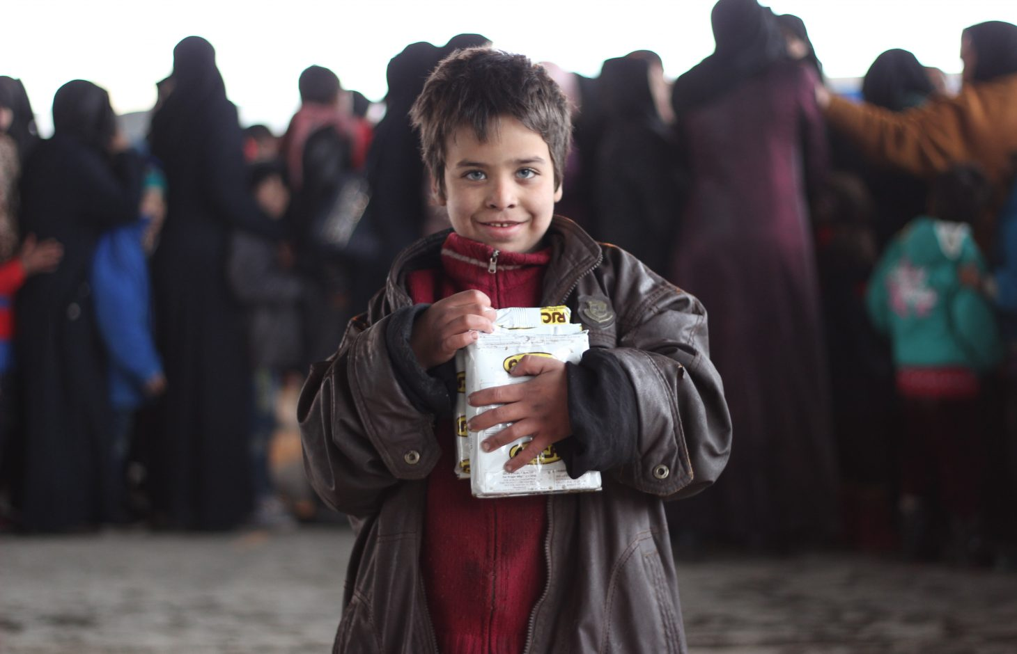On 7 December 2016, A child holds a box of high-energy biscuits distributed by UNICEF to children in a large warehouse in Jibreen, now used as a shelter for thousands of families who fled violence in east Aleppo. UNICEF is screening children for malnutrition in Jibreen and nutritional supplements for children who have survived for weeks and months with just the bare minimum of food.Some 31,5000 people are reported to have been displaced from and within eastern Aleppo City since 24 November. Temperatures are dropping quickly and heavy rainfall has made conditions even worse over the past few days. UNICEF is providing blankets and winter clothing, as well as access to safe water, essential medical care, including vaccinations and psychosocial support for children who have lived through such horrors.In Jibreen, to the east of Aleppo City, children and their families displaced by recent fighting in eastern Aleppo take shelter in a large warehouse in an area under Government control. Some 8,000 people are sheltering there.In Hanano, in east Aleppo City was the first district to be retaken by Government forces on 27 November. People are now moving back to the area as the frontline of fighting has moved further away. This includes families returning to their homes, as well as displaced families from other areas of east Aleppo.