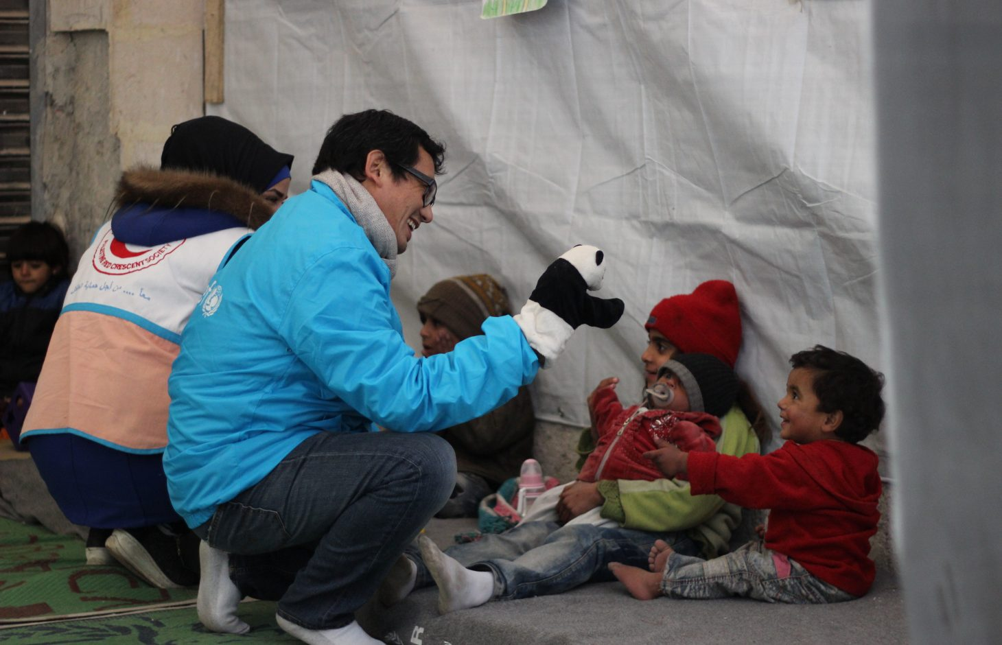 On 29 December 2016, UNICEF-supported volunteers entertain children at a child-friendly space in Jibreen. The makeshift center engages children aged 6-18 in recreational and educational activities as a form of psychosocial support. Volunteers also identify children in need of special care and refer them to local service providers.  Some 31,5000 people are reported to have been displaced from and within eastern Aleppo City since 24 November. Temperatures are dropping quickly and heavy rainfall has made conditions even worse over the past few days. UNICEF is providing blankets and winter clothing, as well as access to safe water, essential medical care, including vaccinations and psychosocial support for children who have lived through such horrors.  In Jibreen, to the east of Aleppo City, children and their families displaced by recent fighting in eastern Aleppo take shelter in a large warehouse in an area under Government control. Some 8,000 people are sheltering there.  In Hanano, in east Aleppo City was the first district to be retaken by Government forces on 27 November. People are now moving back to the area as the frontline of fighting has moved further away. This includes families returning to their homes, as well as displaced families from other areas of east Aleppo.